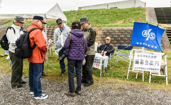 河川敷駐車場の受付で雨の中を参加いただいた会員さんに、祭りの撮影ポイントをご案内。